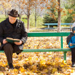 Elderly man and small boy sitting on a park bench — Stock Photo