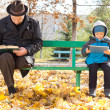 Elderly man and small boy sharing a park bench — Stock Photo