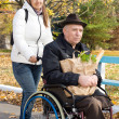 Smiling woman helping her disabled father — Stock Photo