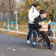 Carer pushing a disabled man in a wheelchair — Stock Photo