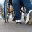 Feet of person pushing wheelchair — Stock Photo #34175605