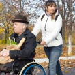 Stock Photo: Happy womhelping handicapped man