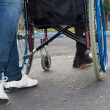 Legs of a carer pushing a wheelchair — Stock Photo