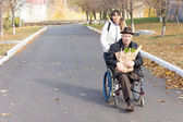 Senior handicapped man with a female carer — Stock Photo