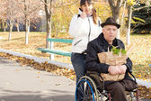 Woman helping an elderly disabled man — Stock Photo
