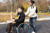 Happy woman helping a disabled elderly man — Stock Photo