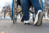 Feet of a person pushing a wheelchair — Stock Photo