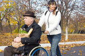 Happy woman helping a handicapped man — Stock Photo