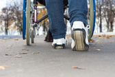 Person pushing a wheelchair down the street — Stock Photo