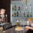 Barman working while a customer drinks at the pub — Stock Photo #35559733