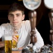Stock Photo: Young man drinking alone