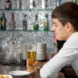 Stock Photo: Young man enjoying a glass of beer with a friend