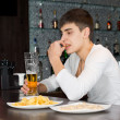 Young man sitting drinking and eating at a pub — Stock Photo #35559757
