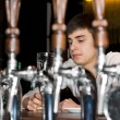 Young man seated at a bar drinking — Stock Photo