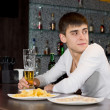 Young man sitting at a bar counter waiting — Stock Photo