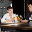Two young men toasting each other over a beer — Stok fotoğraf