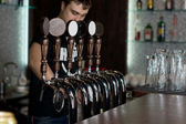 Bartender dispensing draught beer — Stock Photo