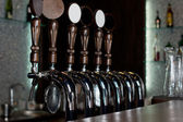 Row of beer taps on a stainless steel keg in a pub — Stock Photo