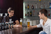 Barman chatting to a customer — Стоковое фото