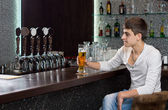 Man drinking beer alone on a pub — Stock Photo