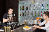 Barman working while a customer drinks at the pub — Stock Photo