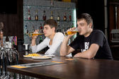 Two men relaxing at the bar drinking beer — Stockfoto