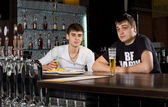 Two teenage men drinking at the pub — Stock Photo