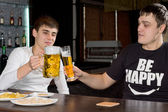 Two men friends drinking beer in a pub — ストック写真