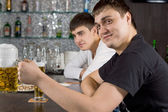 Friendly young man drinking beer at the bar — Stock Photo