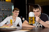 Man eyeing a large tankard of beer in anticipation — ストック写真