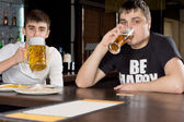 Two men on a boys night out drinking beer — Stock Photo