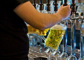 Bartender dispensing a tankard of draught beer — Stock Photo