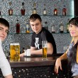 Young couple drinking with the barman at the bar — Stock Photo