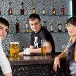 Young couple drinking with the barman at the bar — Stock Photo #35614027