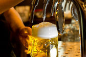 Man pouring a tankard of frothy beer — Stock Photo