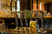 Tankard of beer with beer taps in a pub — Stock Photo