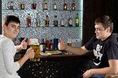 Två män visar tummen när man dricker öl — Stockfoto