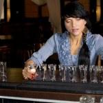 Brunette hostess aligning shot glasses on the bar — Stock Photo #36238257