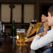 Young man next to his female friend at the bar — Stock Photo