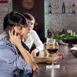 Woman chatting on her mobile at the bar — Foto Stock