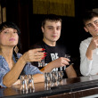 Three young friends downing shots of vodka — Stock Photo