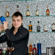 Stock Photo: Bartender mixing liquors with cocktail shaker