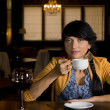 Solitary woman drinking at the bar a cup of coffee — Stock Photo