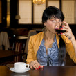 Stock Photo: Womdrinking wine and coffee at bar counter