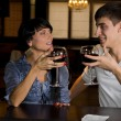 Young couple drinking red wine at a bar counter — Foto Stock