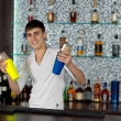 Happy young barman mixing cocktails — Stock Photo