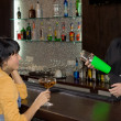 Barman mixing a cocktail for a female customer — Stock Photo