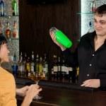 Friendly barman chatting to a female customer — Stock Photo #36238681