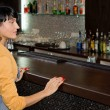 Young woman waiting for service at the bar counter — Stock Photo