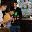Young couple laughing as they drink at a bar — Stock Photo